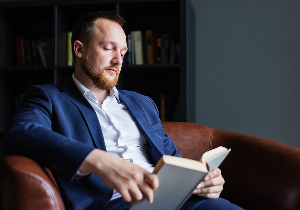 Middle-aged man sitting in home library reading book - Radiant Health SF Men's Health