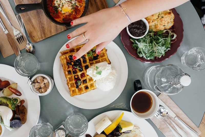 Woman's hand reaching for waffles on a table of food