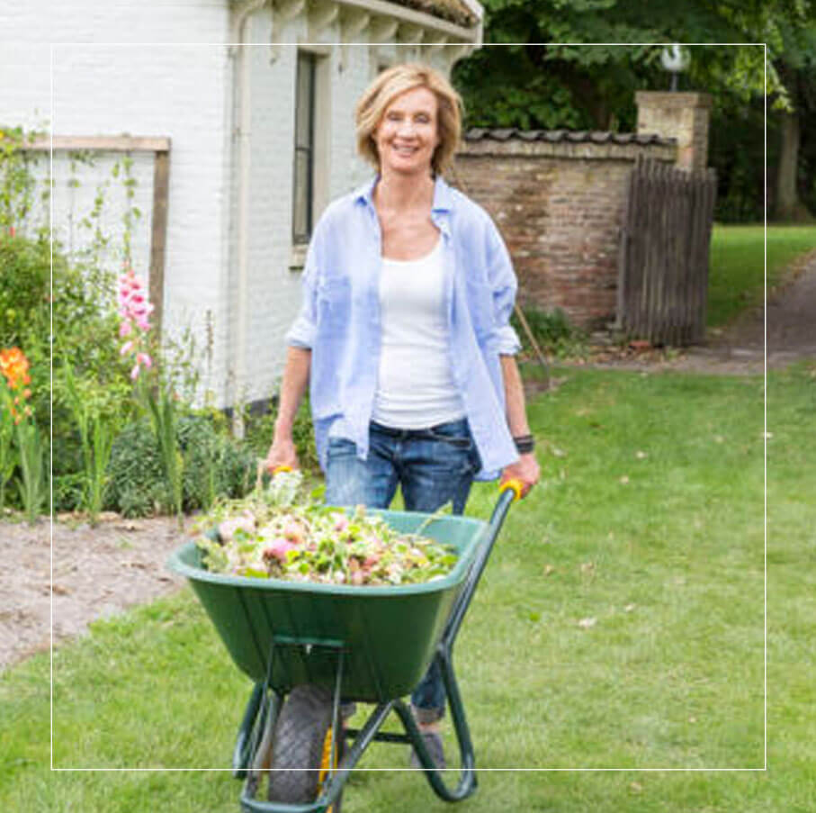 Picture of Inge van Haselen outside pushing a wheel barrel with flowers
