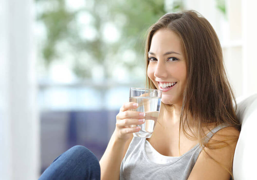 Young casual smiling woman sitting on a couch drinking a glass of water