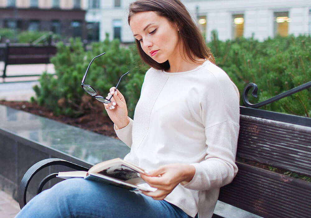 Young woman sitting outside on a bench holding eye glasses and looking at a book