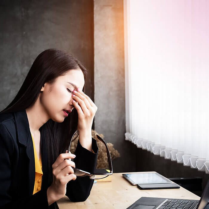 Young woman in office at desk with headache, fatigue - Radiant Health SF Adrenal Fatigue Syndrome