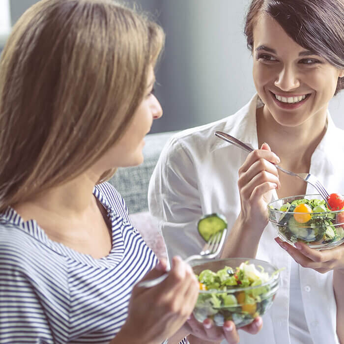 Two young smiling women eating salad - Radiant Health SF Detoxification