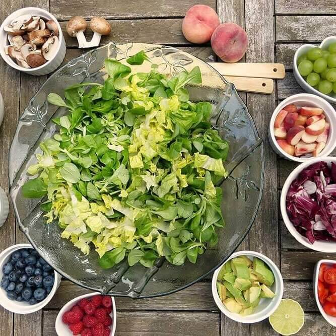 Big salad bowl with different healthy food options around it