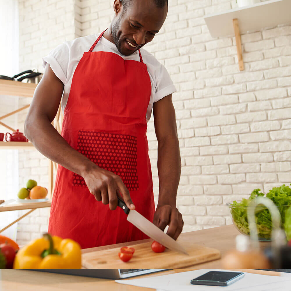 Young African American man chopping tomato - Radiant Health SF Detoxification