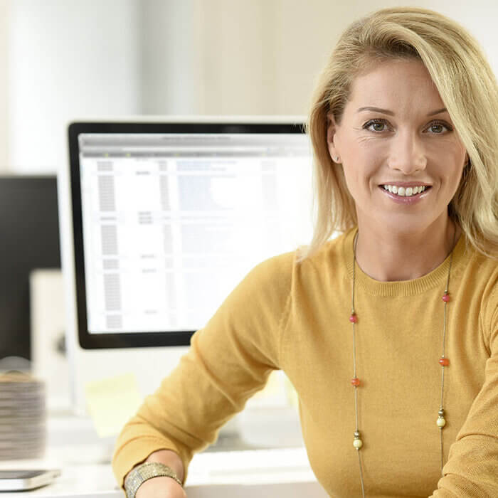 Smiling middle-aged business woman in office in front of computer - Radiant Health SF Menopause Support